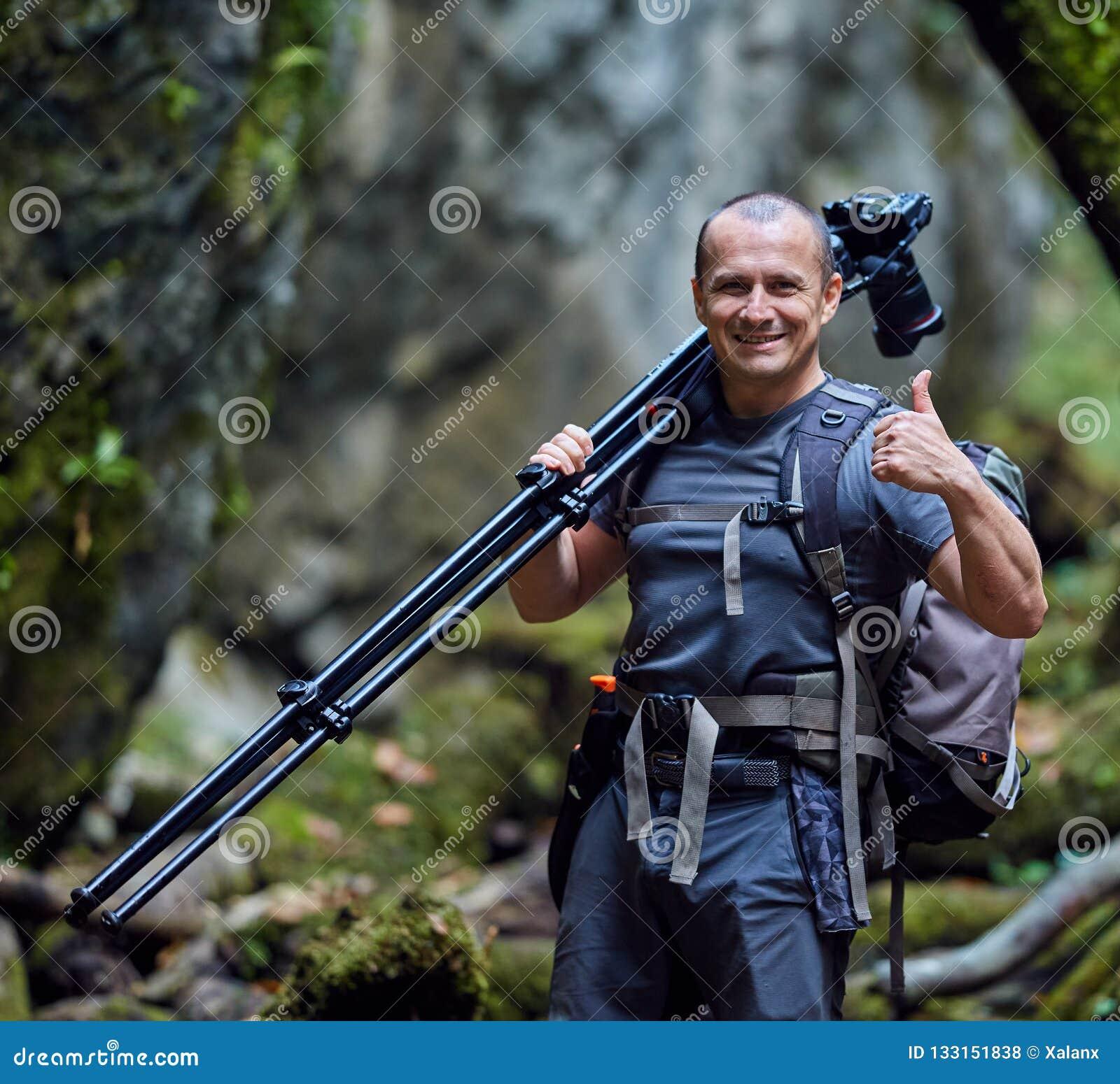 Professionele aardfotograaf met camera op driepoot