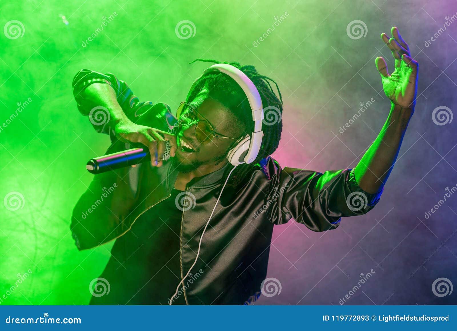 Professionele Afrikaanse Amerikaanse club DJ in hoofdtelefoons die met microfoon zingen