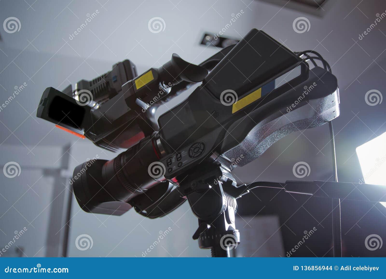 Professionele digitale Mirrorless-camera met microfoon op de video van de driepootopname Zijaanzicht van digitale videocamera Cam