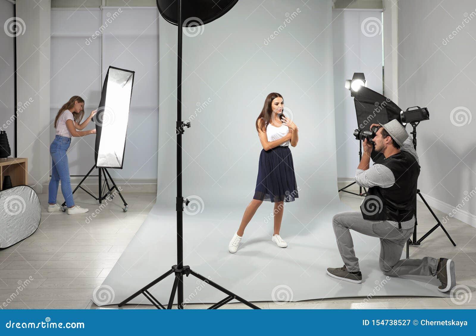 Professionele fotograaf met hulp nemend beeld van jonge vrouw in studio