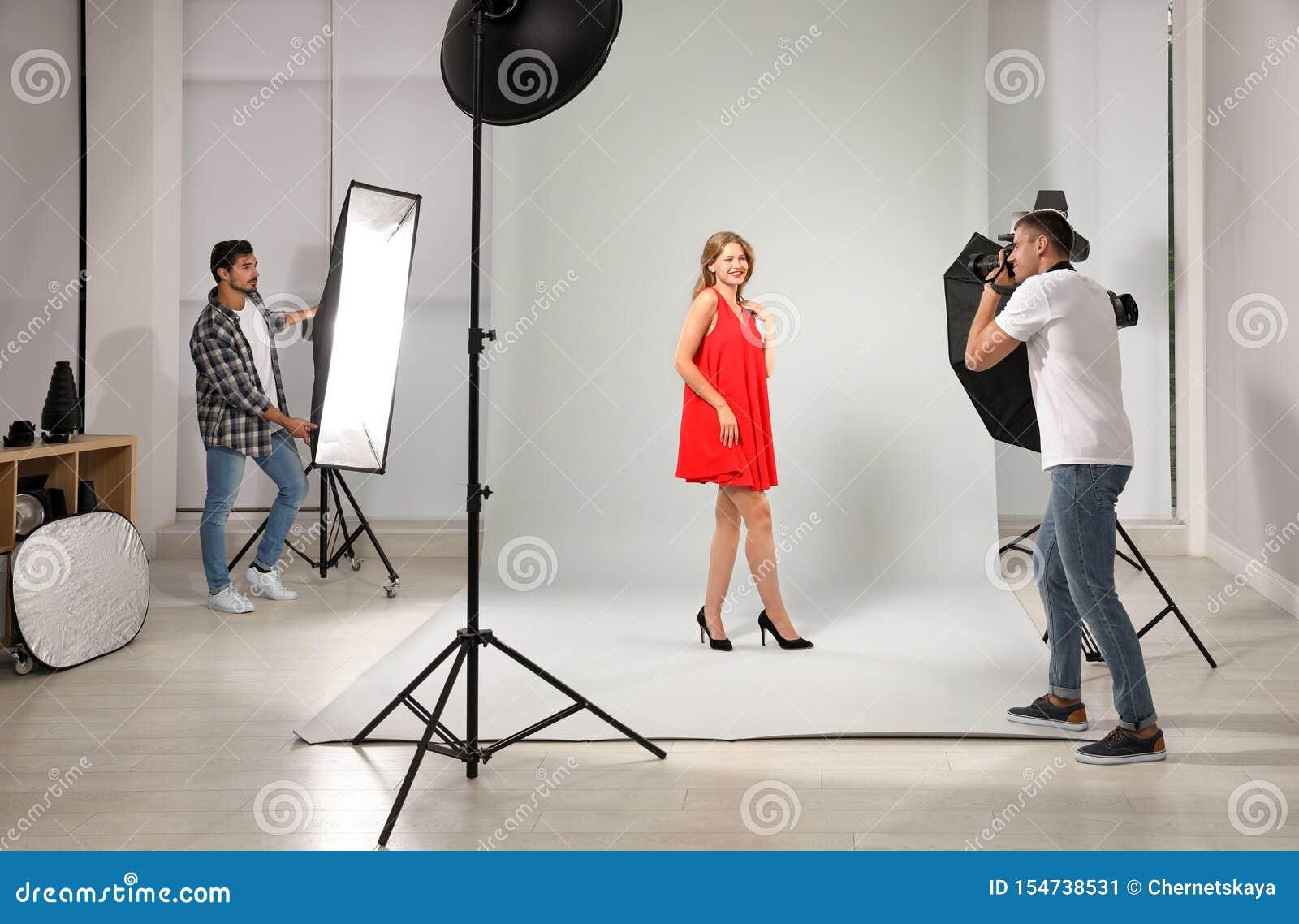 Professionele fotograaf met hulp nemend beeld van jonge vrouw