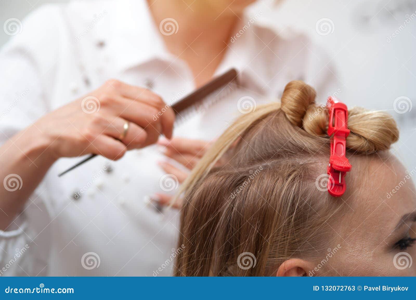 Professionele kapper die een kapsel maken aan een blond model