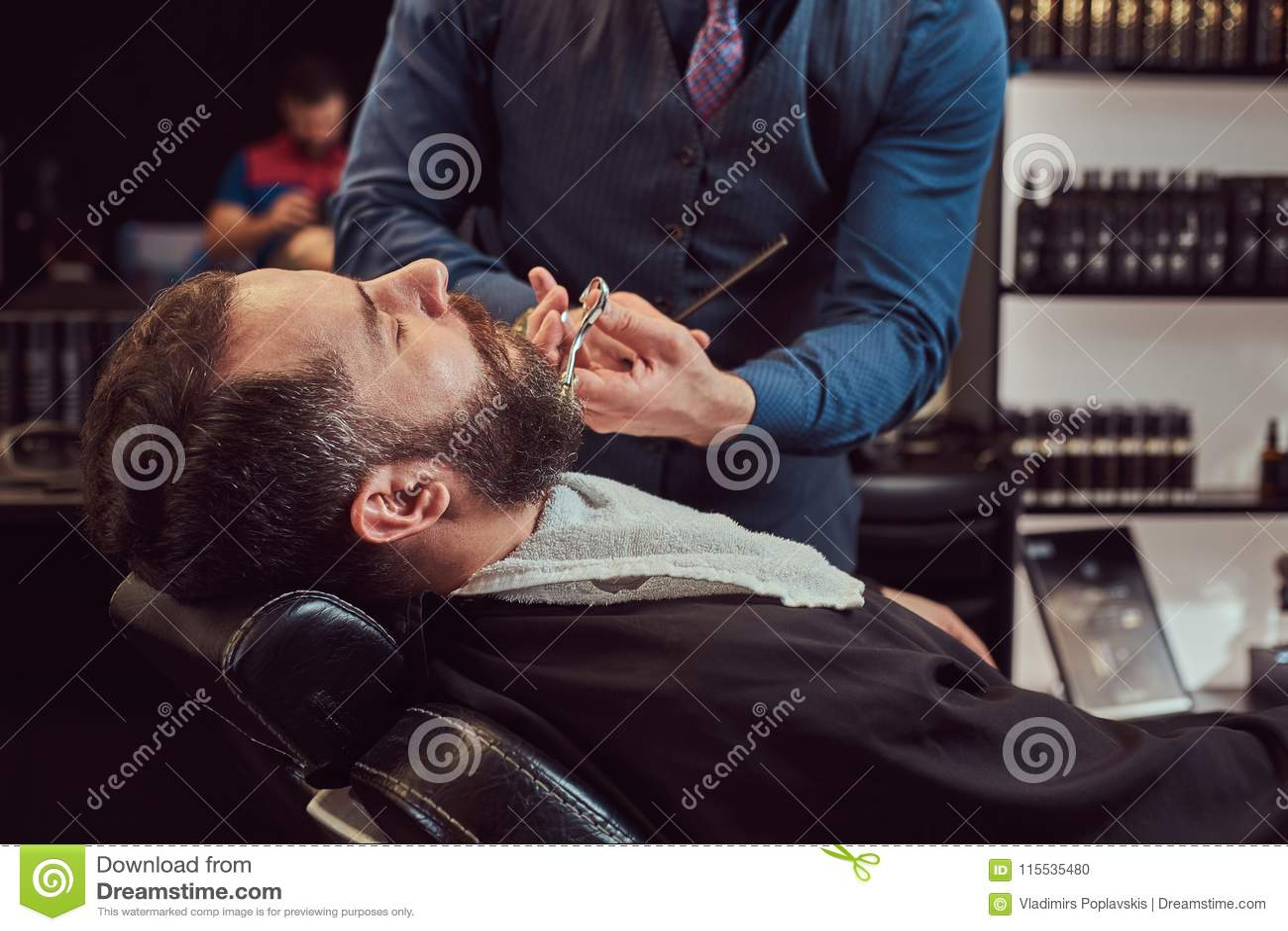 Professionele kapper modelleringsbaard met schaar en kam bij de herenkapper