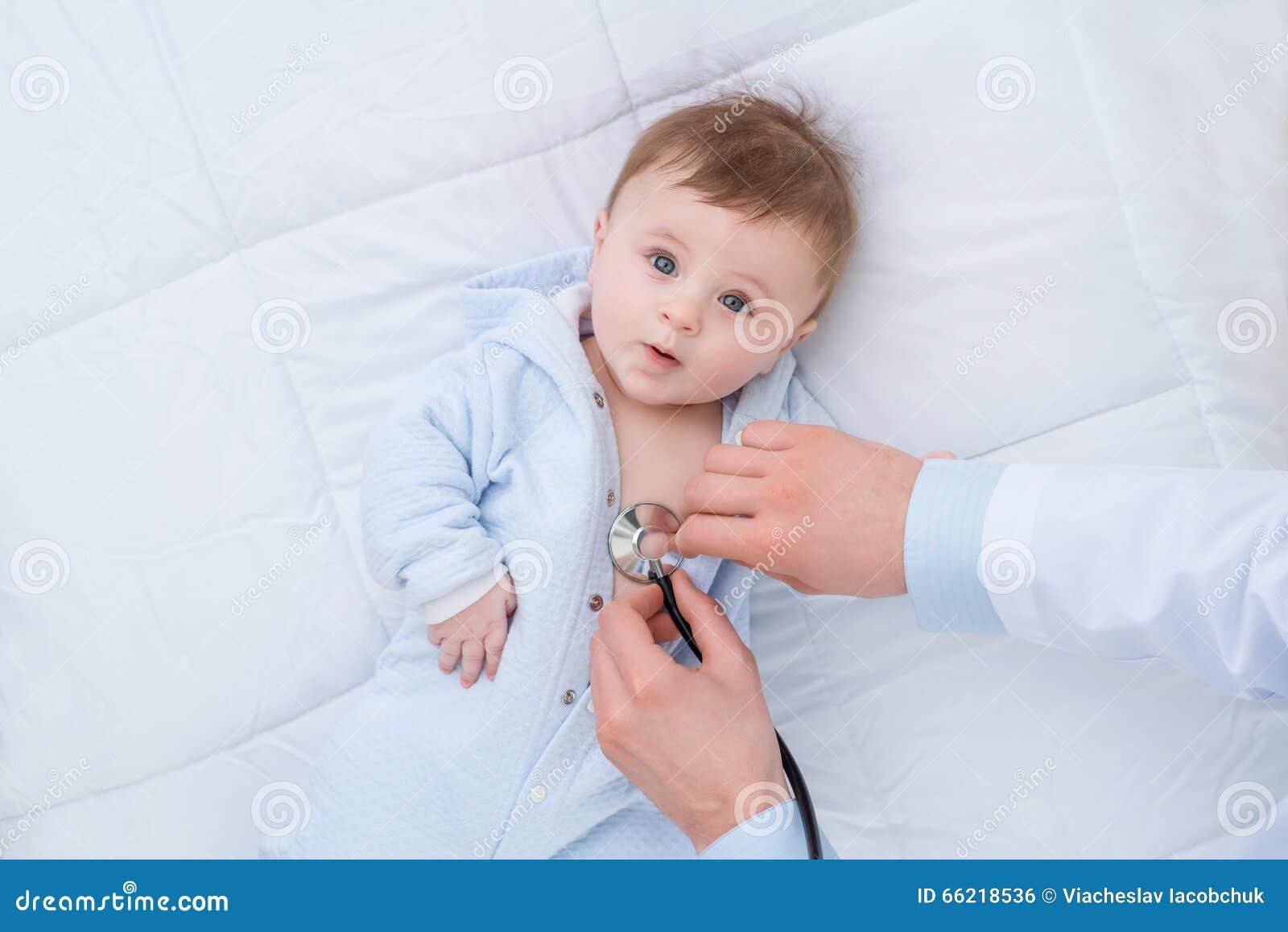 Professionele pediater die zuigeling onderzoeken