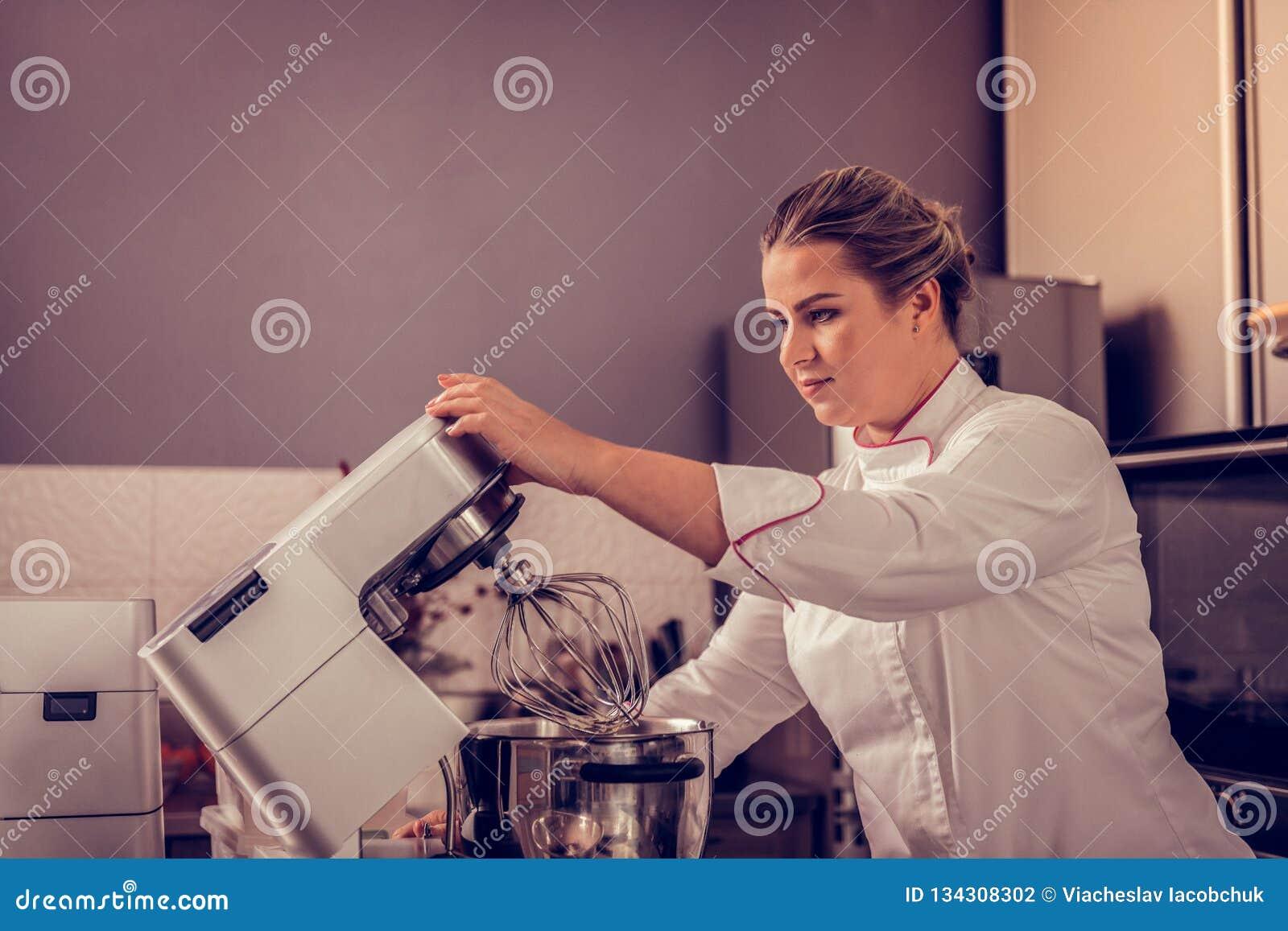 Professionele vrouwelijke gebakjechef-kok die keukenmachine met behulp van