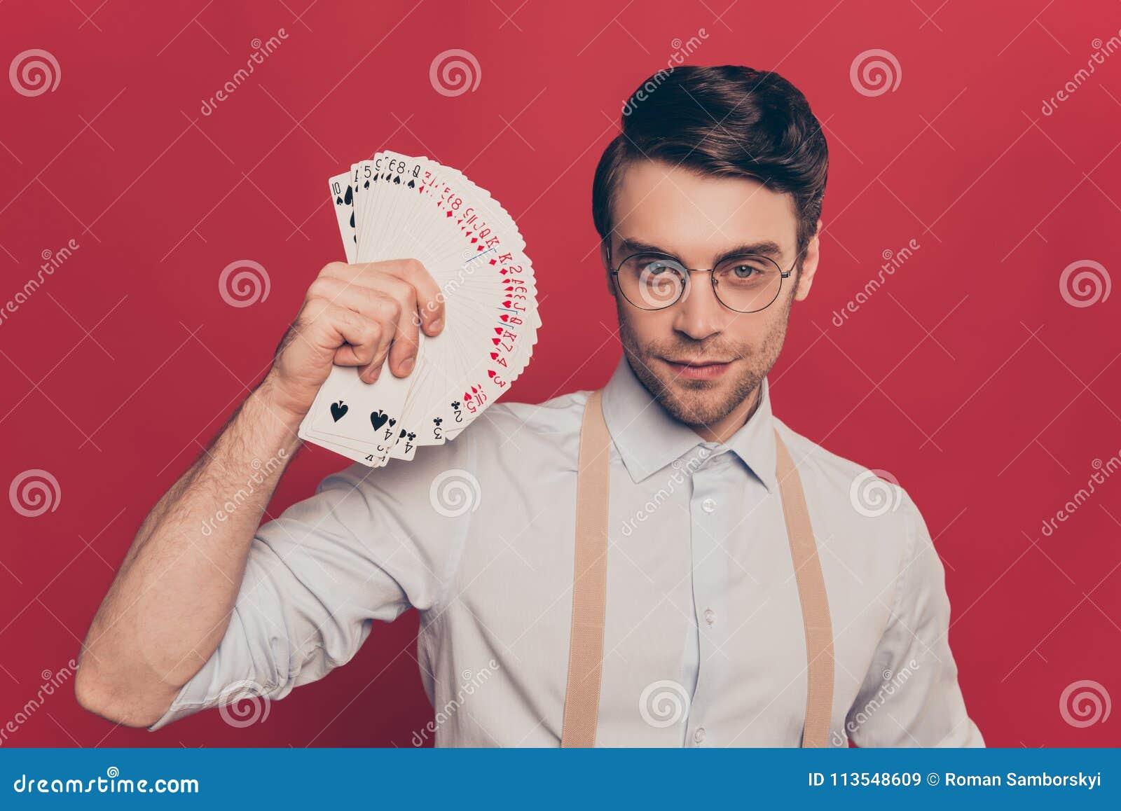 Professionell listig trollkarl, illusionist, hasardspelare i den tillfälliga dräkten, exponeringsglas, innehav, fastställt däck f