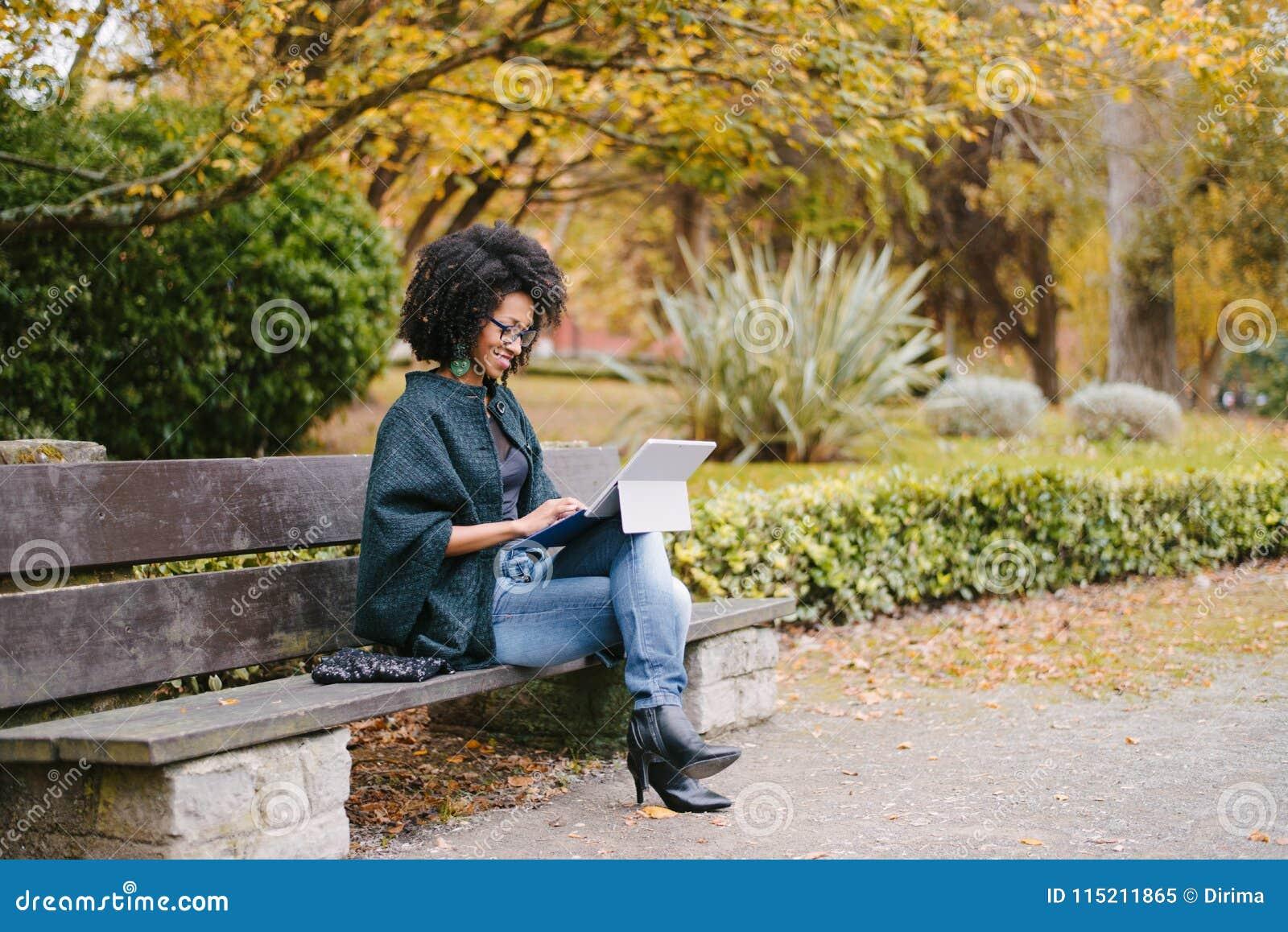 Professionelle schwarze Frau, die mit Laptop draußen im Herbst arbeitet