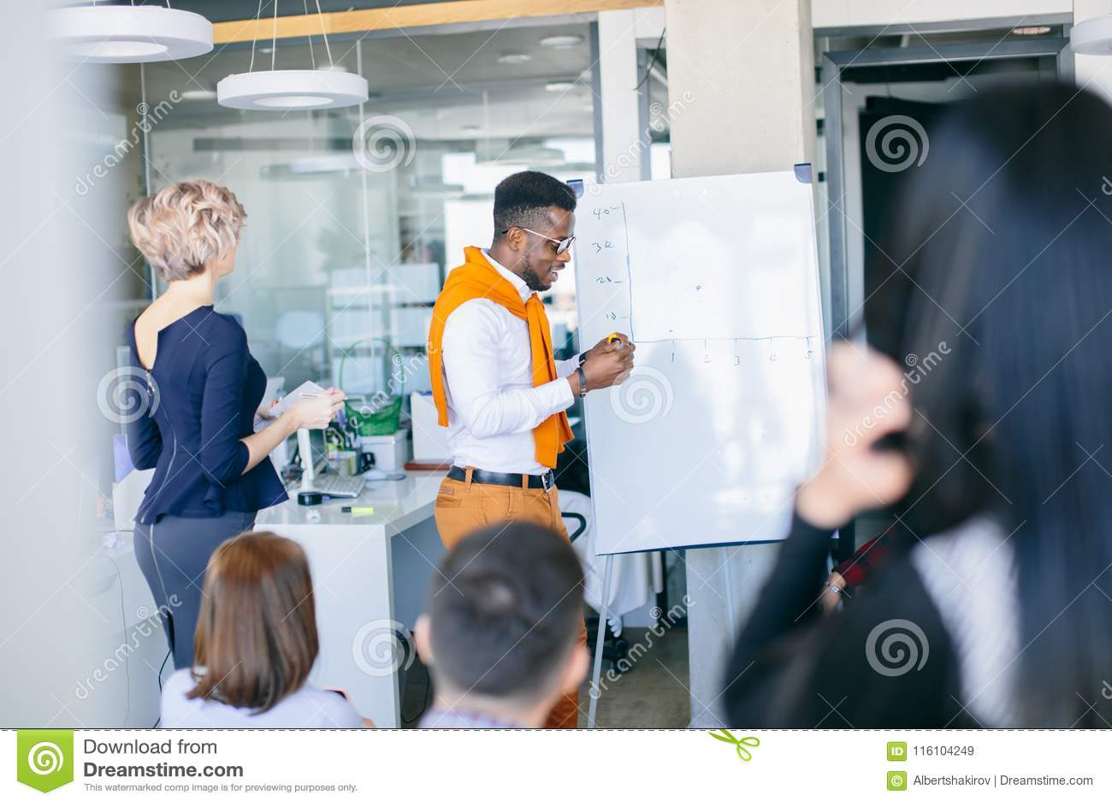 Professioneller schwarzer Tutor, der Training vor flipchart zur Verfügung stellt