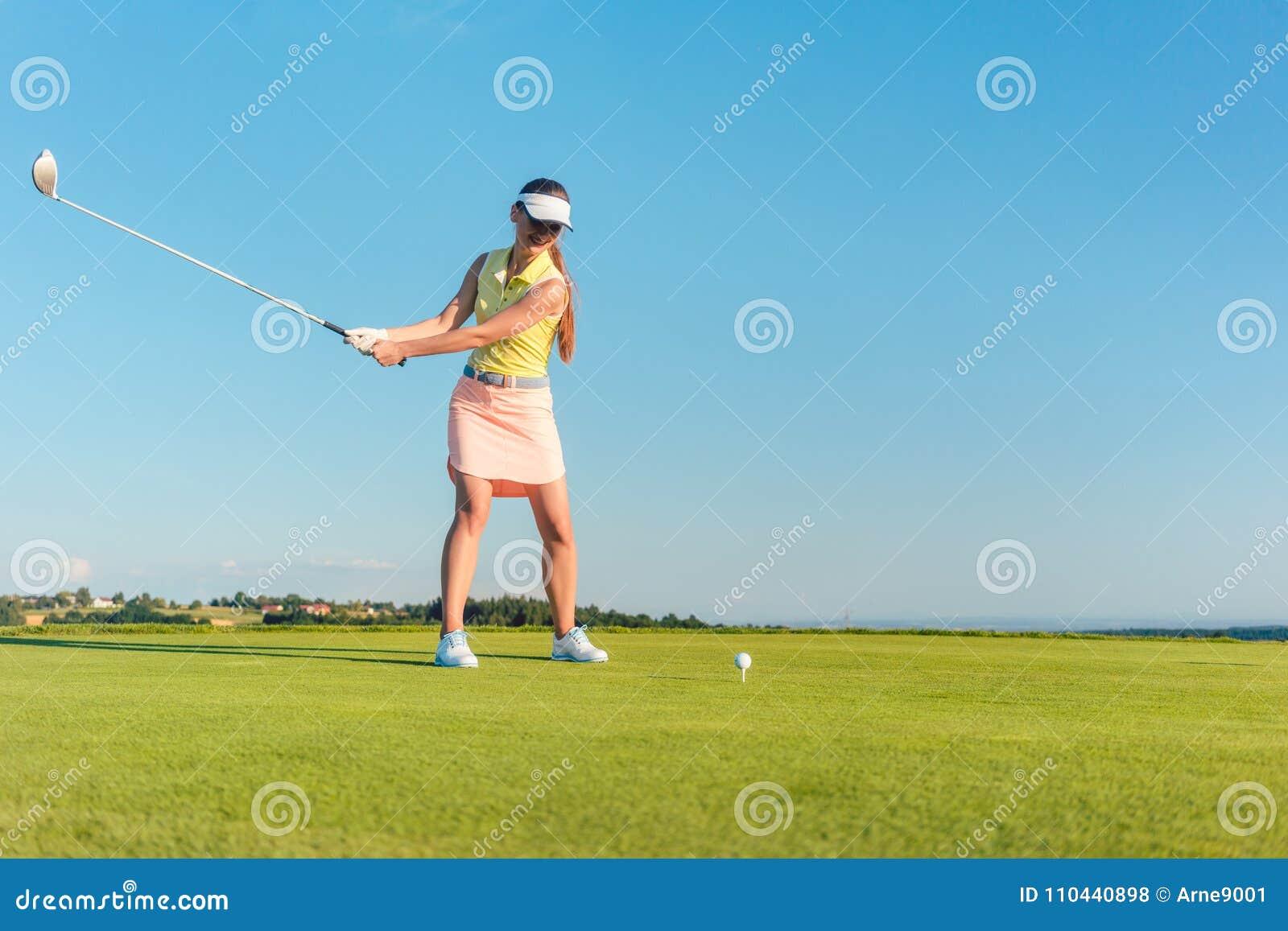 Professioneller weiblicher lächelnder Golfspieler beim Schwingen eines Fahrerclubs