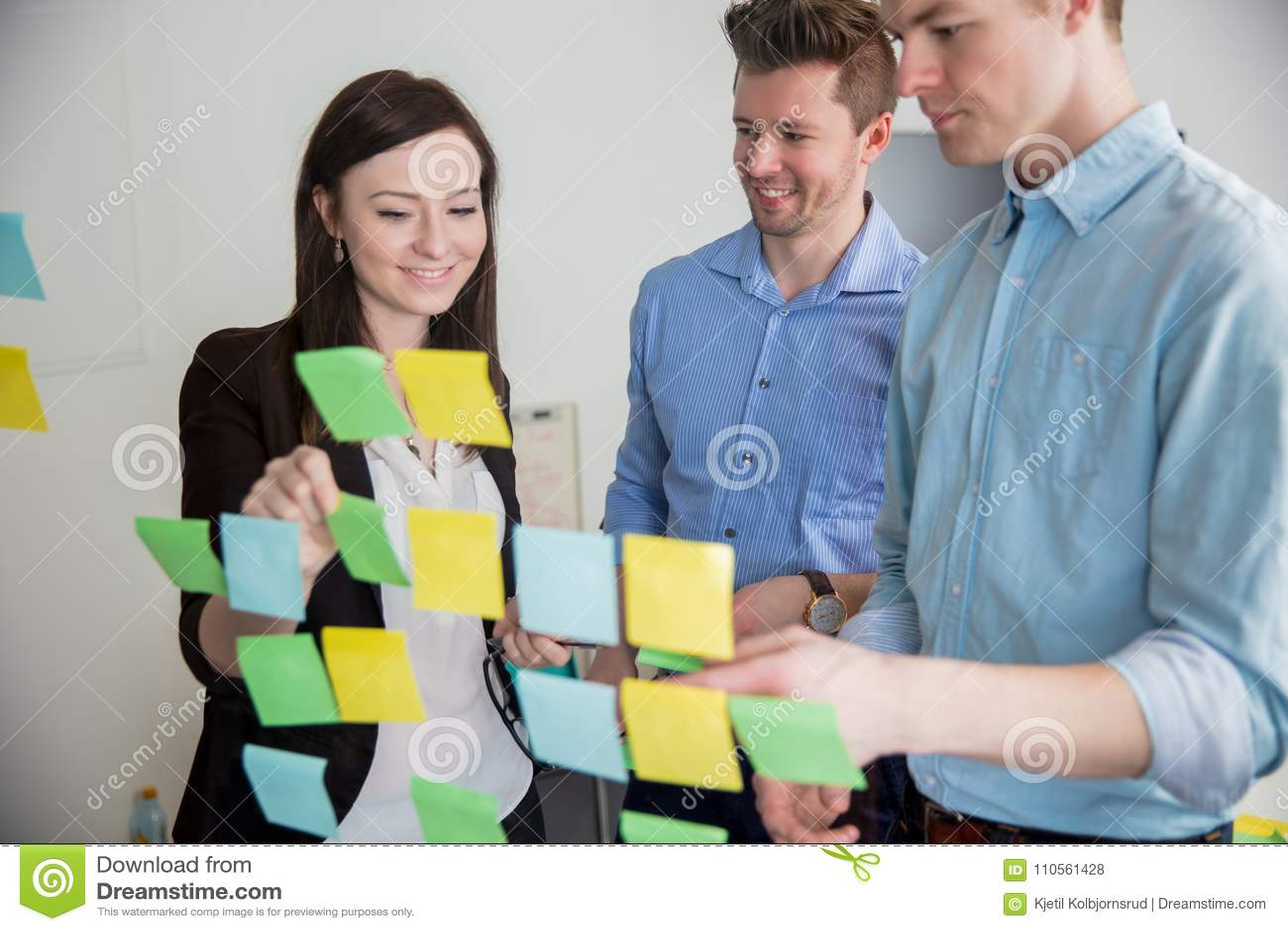 Professionisti di affari che attaccano le note sul vetro in ufficio
