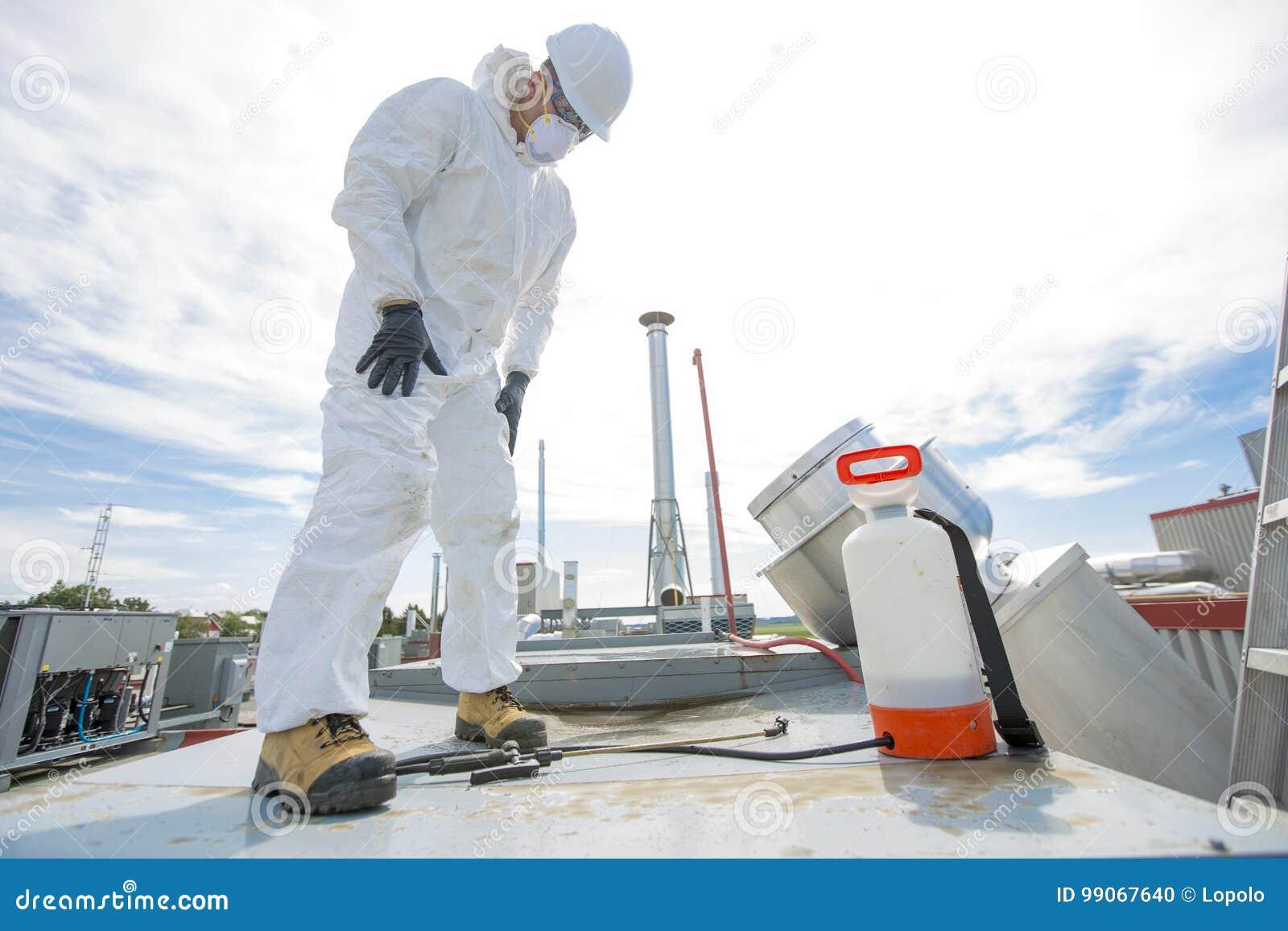 Professionnel dans l uniforme protecteur, masque, gants dans le toit pour le nettoyage