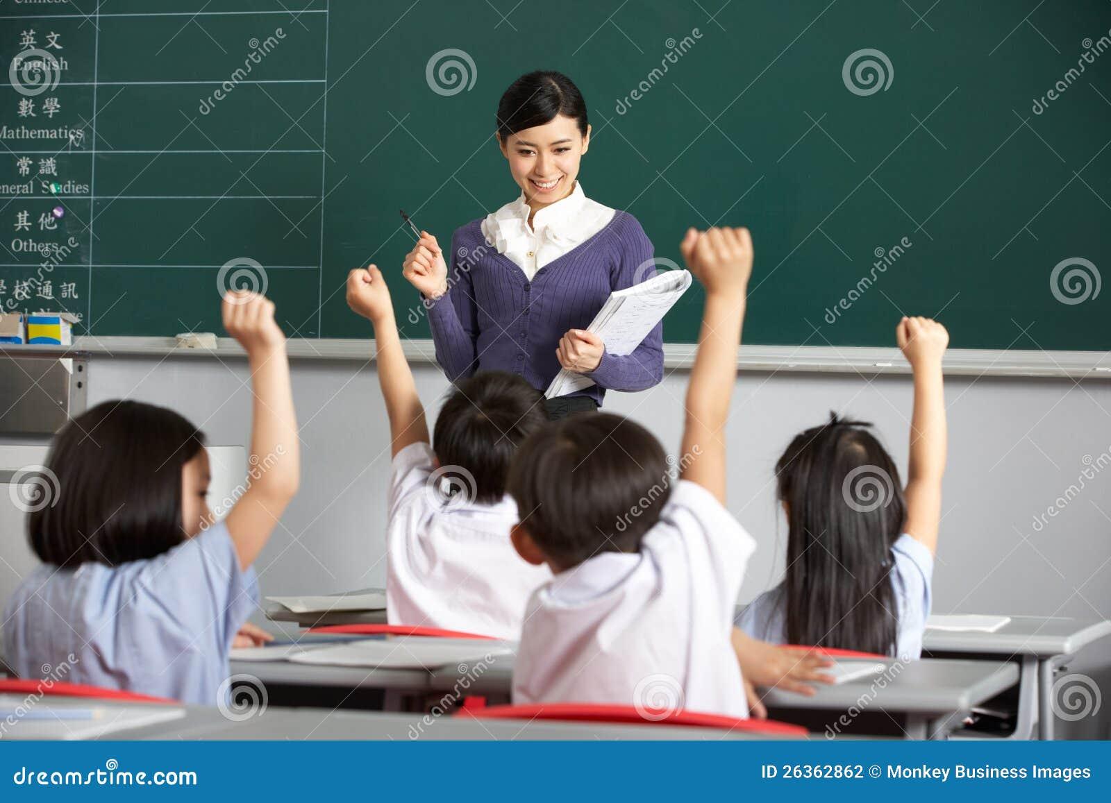 Professor com os estudantes na sala de aula chinesa da escola