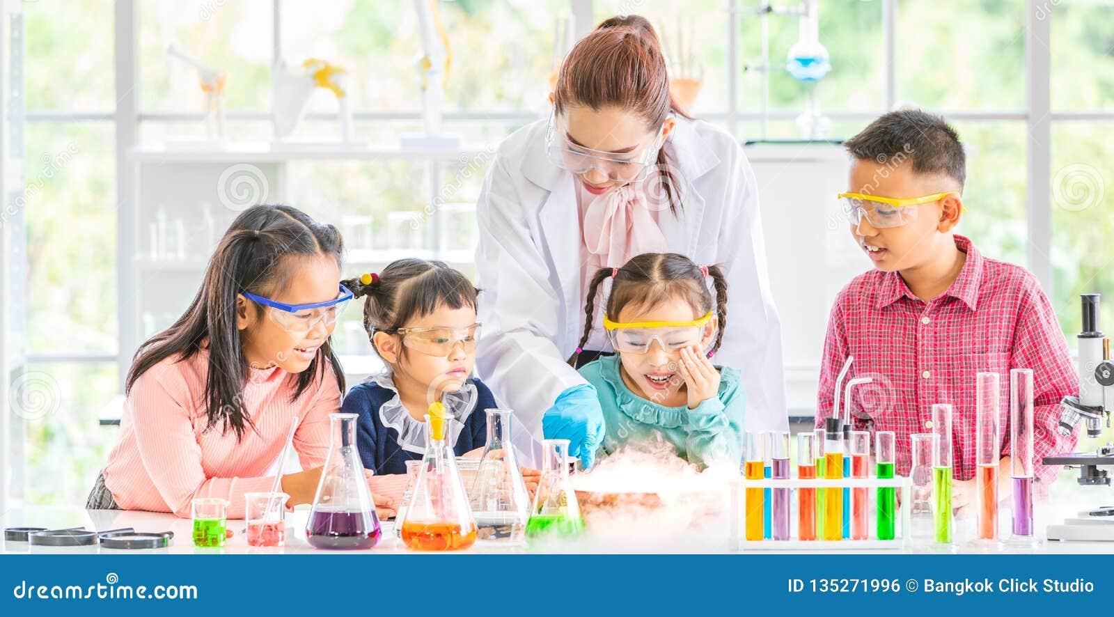 Professor e estudantes no laboratório, flutuador do fumo para fora