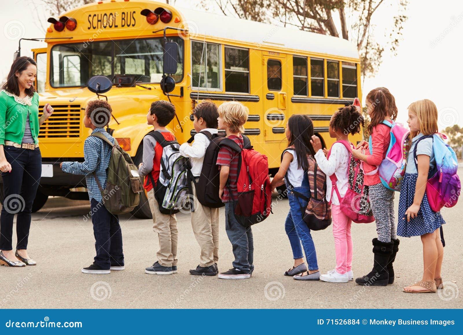 Professor e um grupo de crianças da escola primária em uma parada do ônibus
