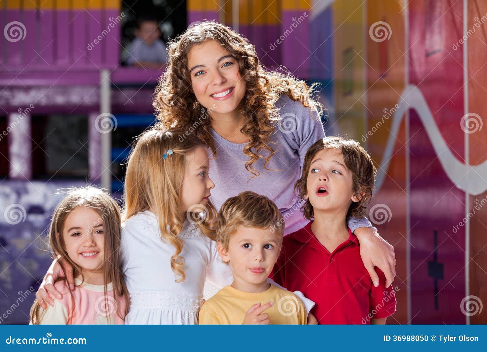 Professor feliz With Cute Children no pré-escolar