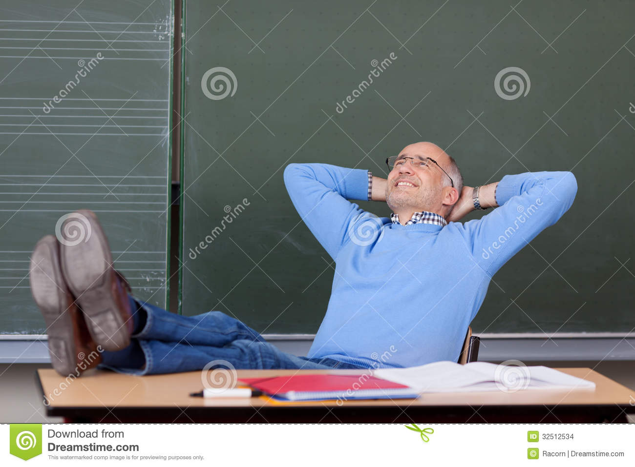 Professor With Hands Behind Head Looking Up At Desk Stock