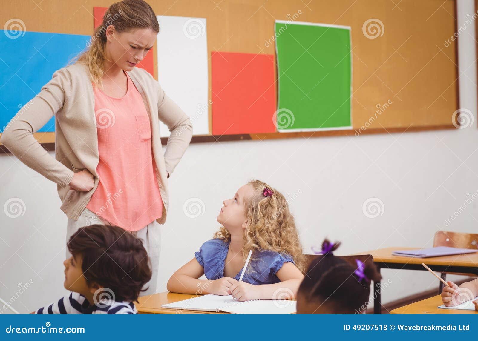 Professor irritado que olha o aluno com mãos nos quadris