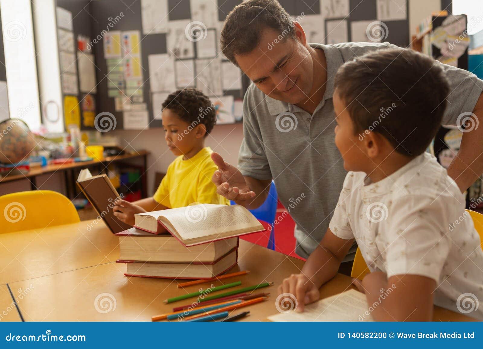 Professor masculino que ensina uma estudante em uma sala de aula