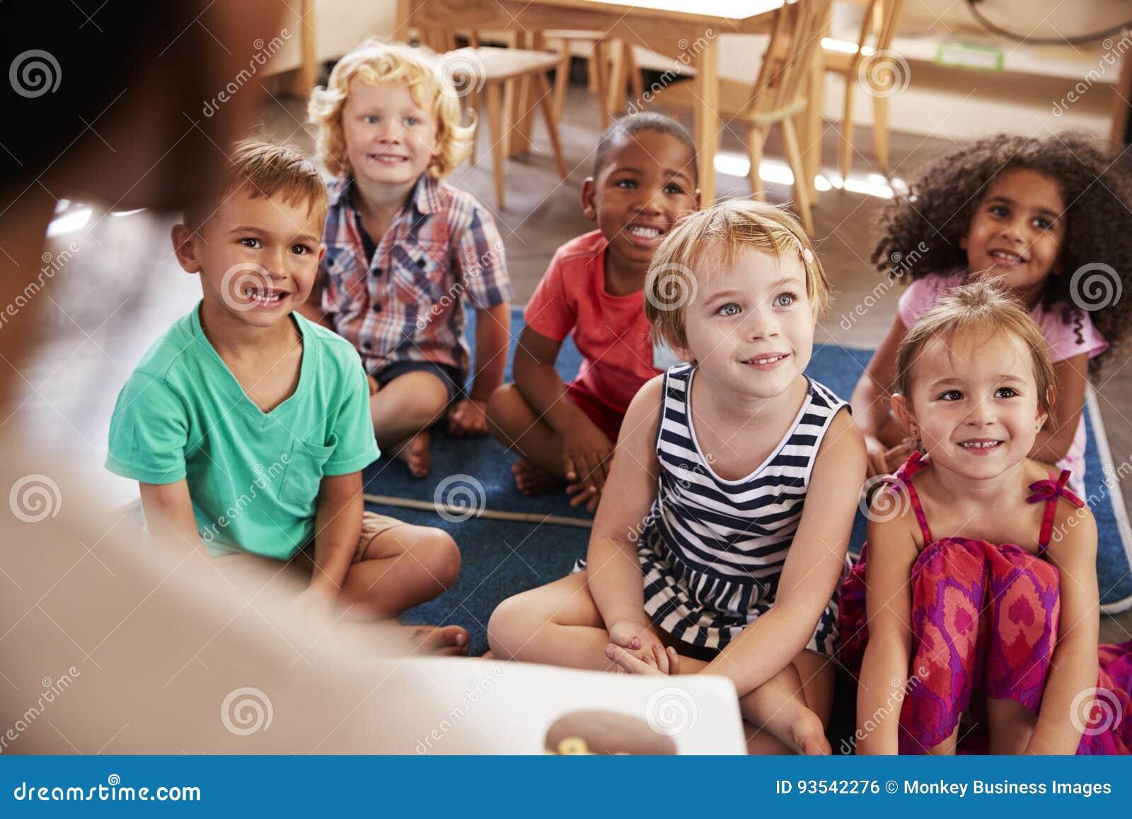 Professor At Montessori School que lê às crianças no tempo da história