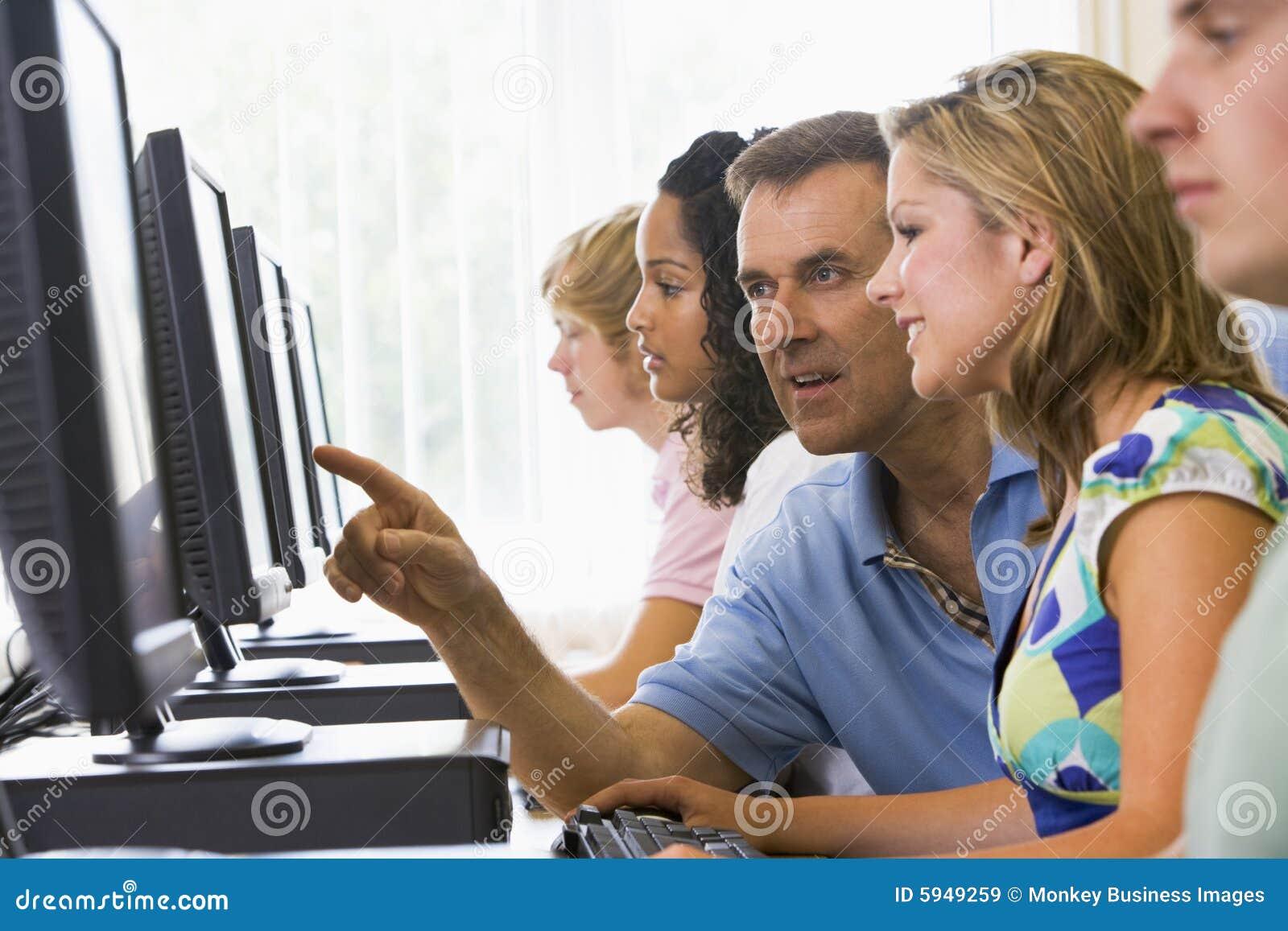 Professor que ajuda ao estudante universitário no laboratório do computador