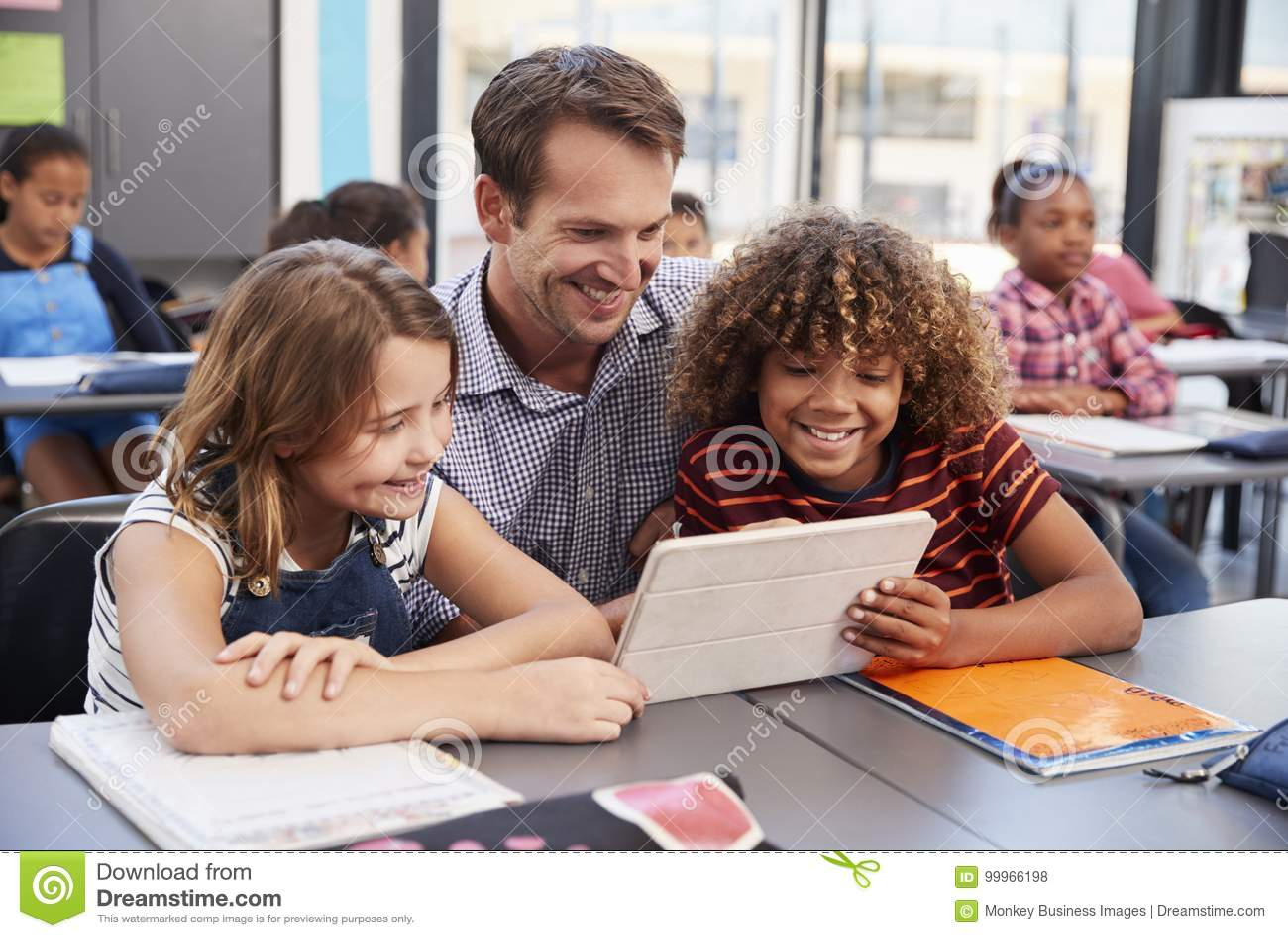 Professor que usa a tabuleta com os dois alunos na turma escolar