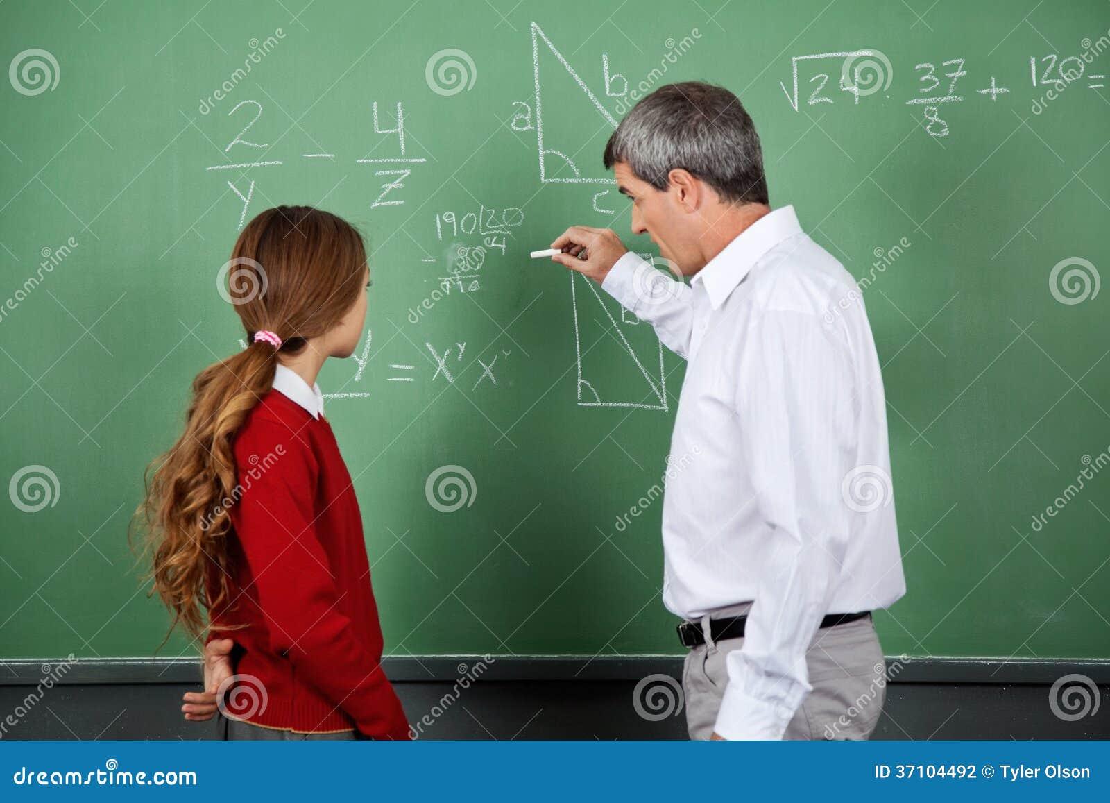 professor teaching mathematics to female student stock