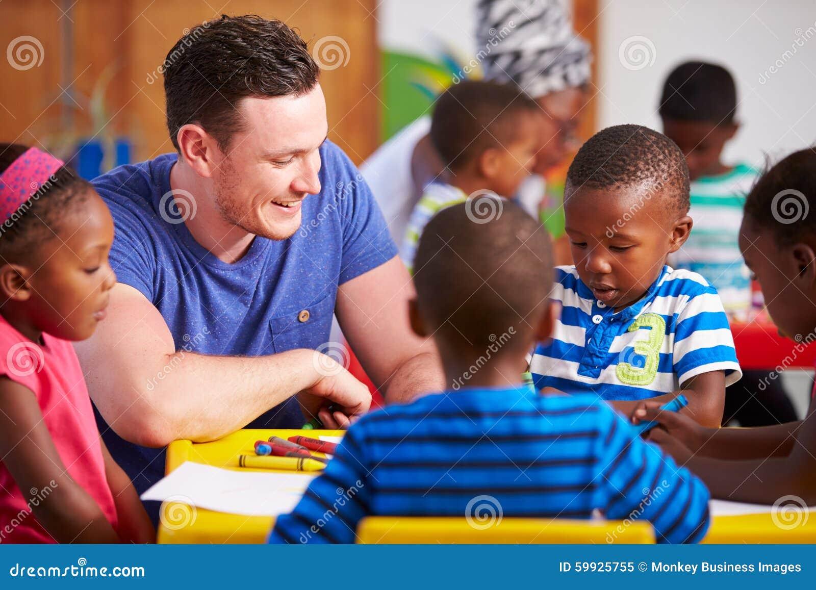 Professor voluntário que senta-se com crianças prées-escolar em uma sala de aula