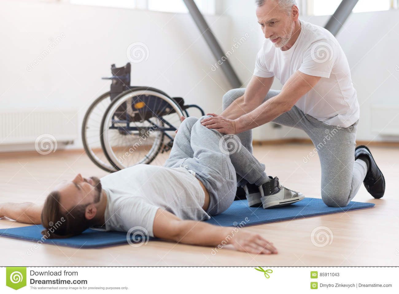 Proficient general practitioner stretching the disabled in the gym