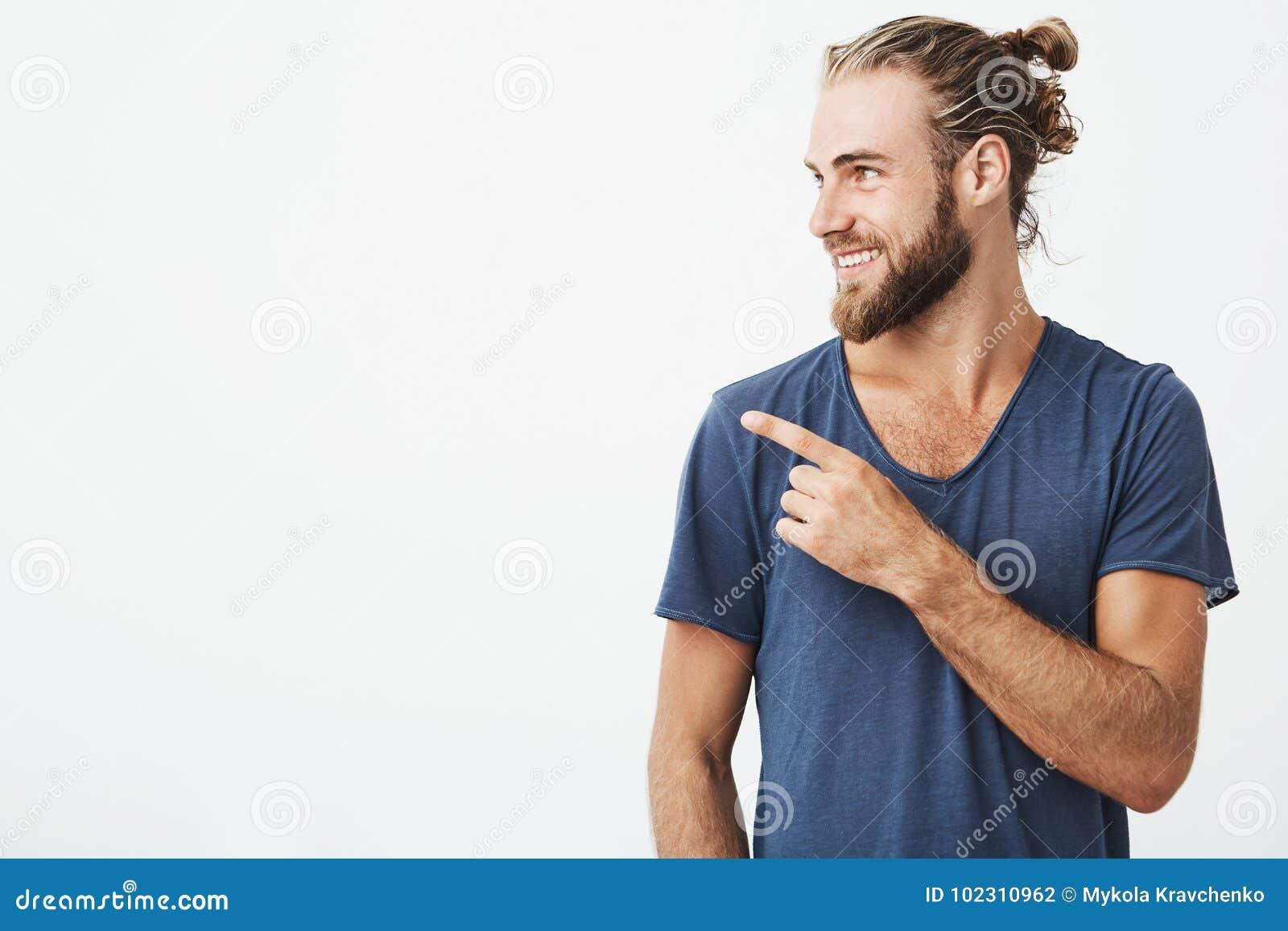 Profiel van de vrolijke knappe mens met modieus kapsel en baard die brightfully en op vrije ruimte richten voor glimlachen