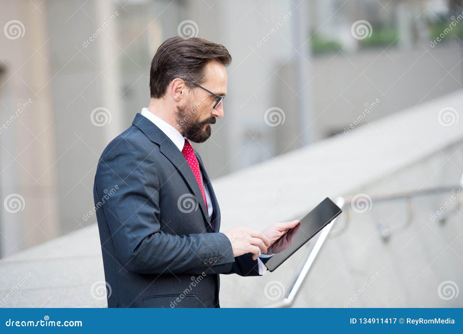 Profiel van geconcentreerde rijpe manager die een tablet in de straat gebruiken
