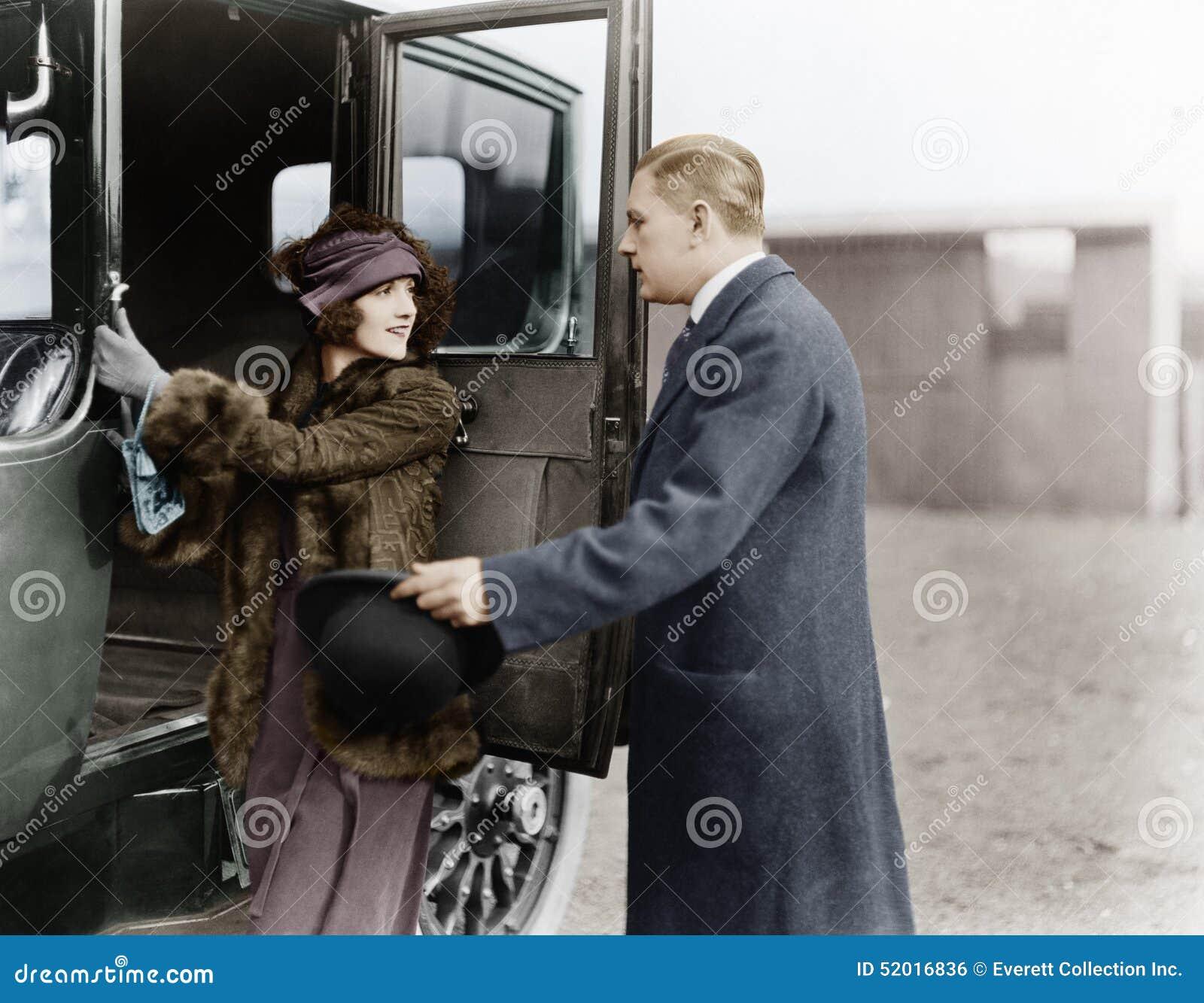 Profil av en man som hjälper en ung kvinna att stiga ombord en bil (alla visade personer inte är längre uppehälle, och inget gods