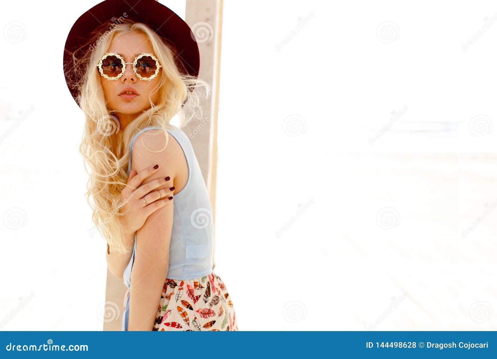 Profil av en sexig blond flicka med runt glasögon, lockigt hår och burgundy hatt som isoleras på havsbakgrunden