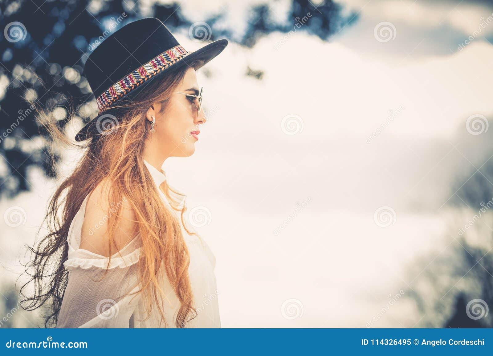 Profil av långt hår för trendig kvinna med hatten och solglasögon