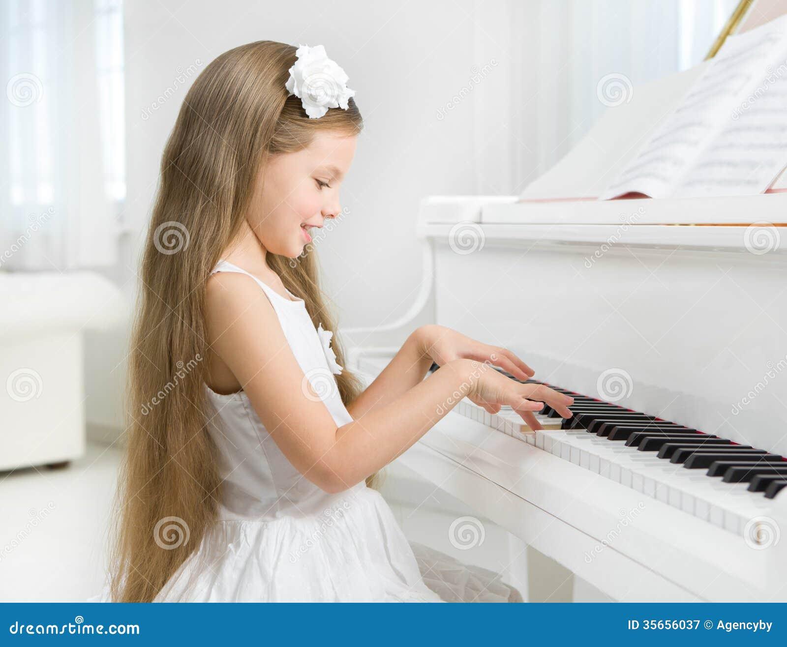 Profil av lilla flickan i den vita klänningen som spelar pianot