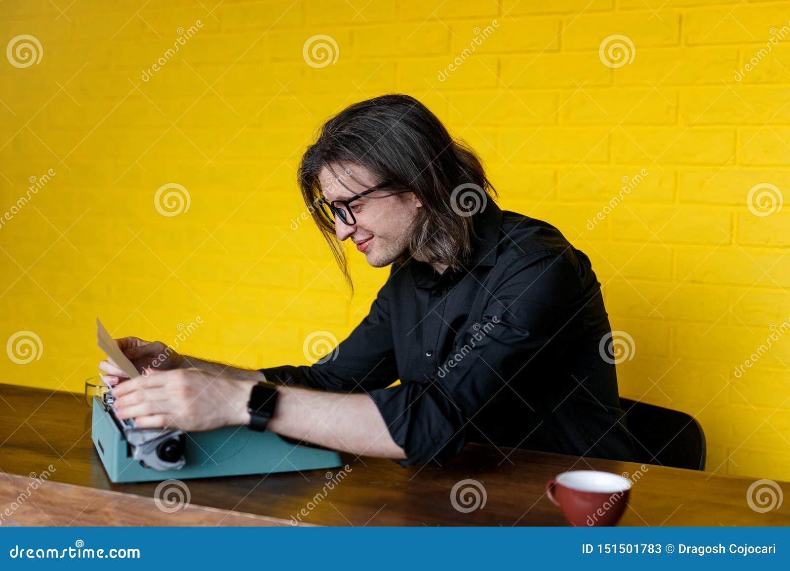Profil d un homme d une manière amusante dans l habillement noir insérant le nouveau papier dans la machine à écrire, au-dessus d