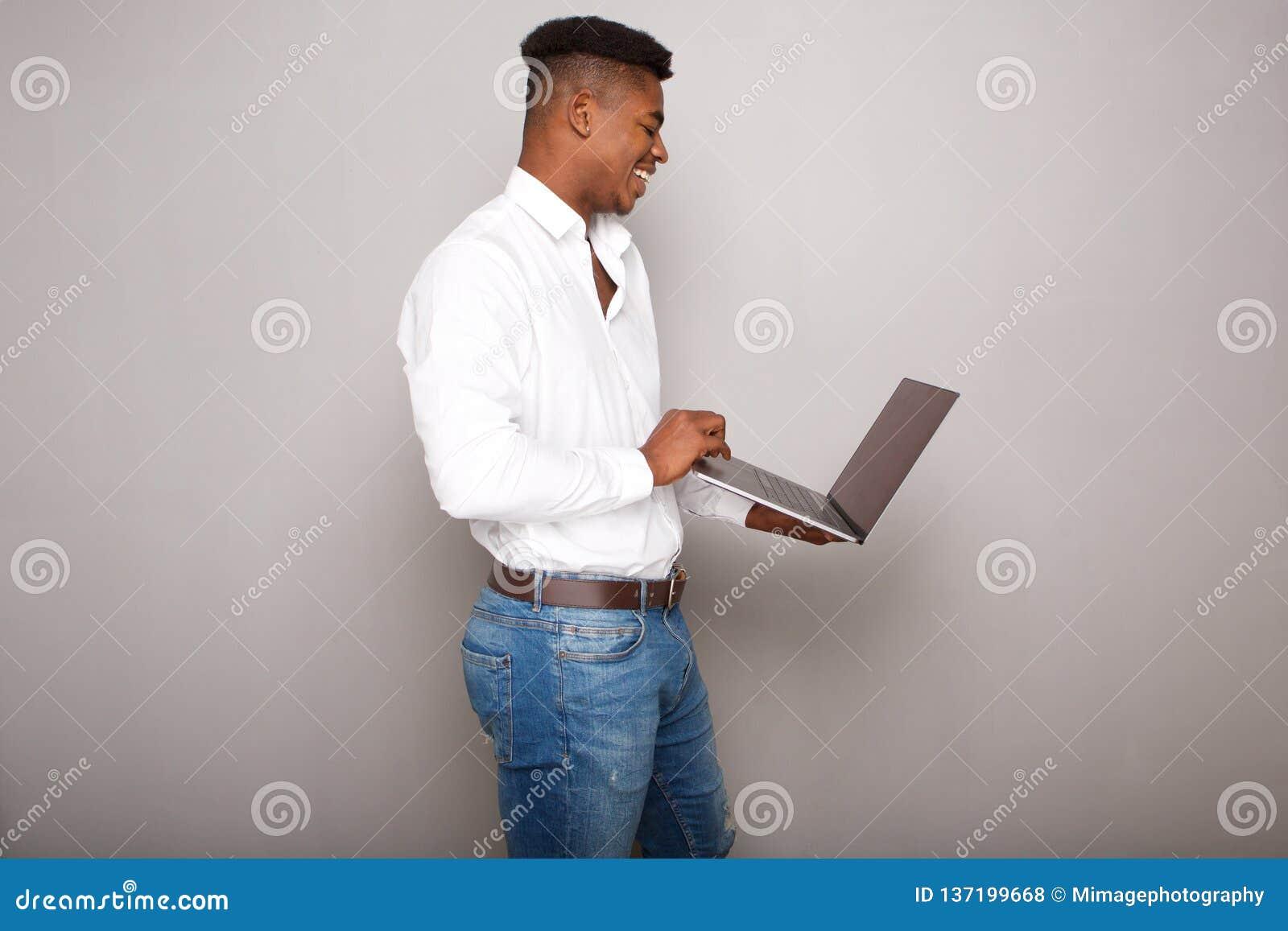 Profil de jeune ordinateur portable heureux de participation d homme de couleur par le mur gris