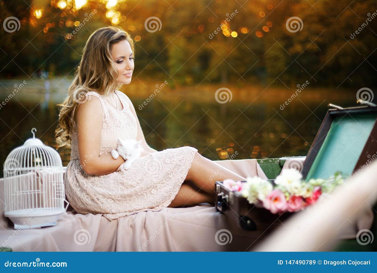 Profil zmysłowa romantyczna dziewczyna, ubierający w lato sukni, sadzającej w łodzi z figlarką w rękach, podczas zmierzchu światł