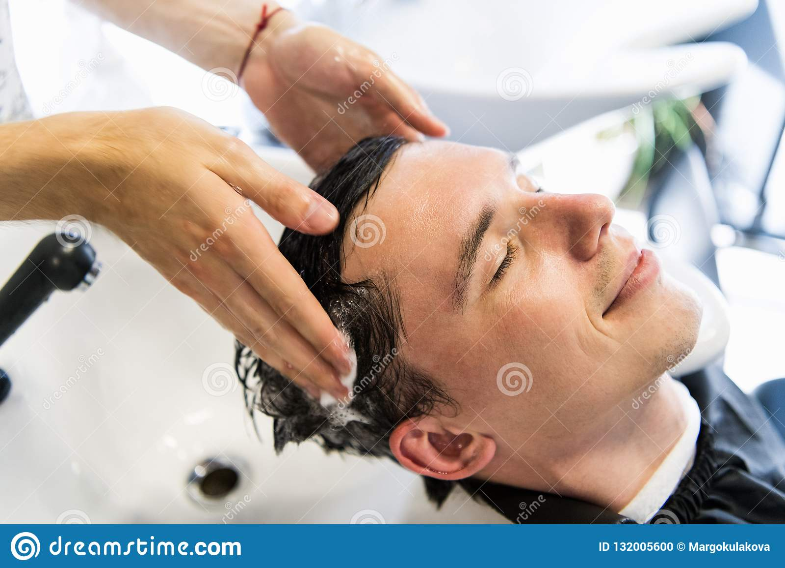 Profilansicht eines jungen Mannes, der sein Haar gewaschen und sein Kopf erhält, massierte in einem Friseursalon