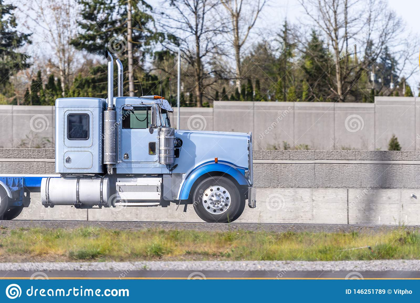 Profile Of Big Rig Blue Semi Truck Tractor Running On The Road For