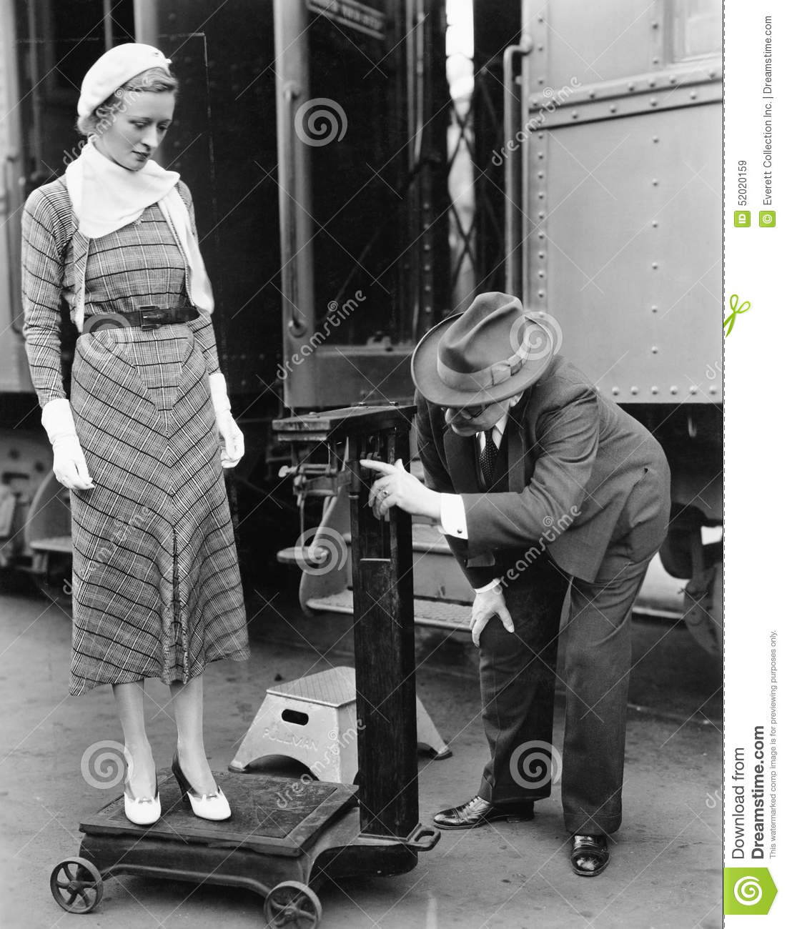 Profile of a man measuring weight of a woman standing on a weighing scale in front of a train