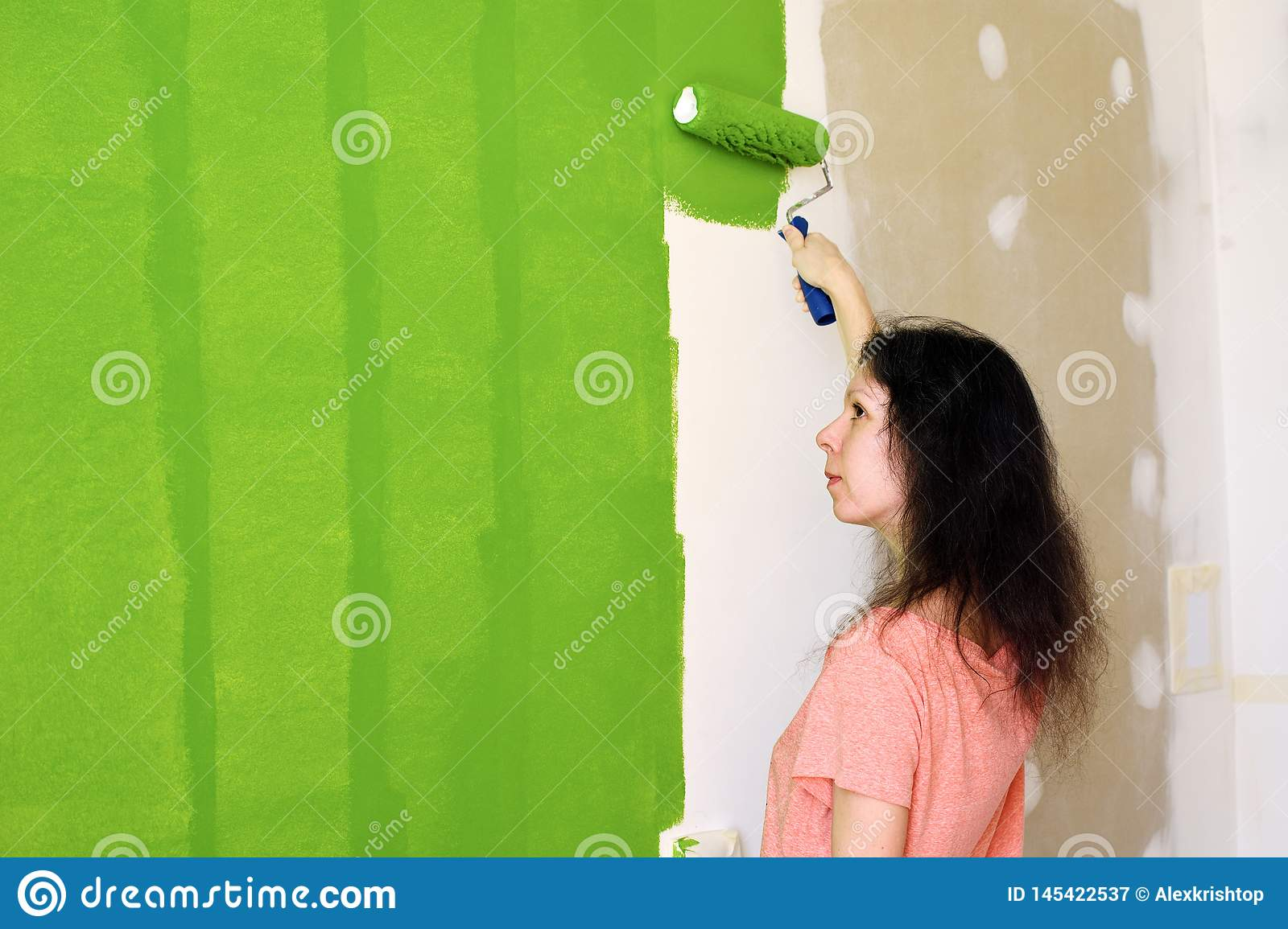 Profile of a pretty young woman in pink t-shirt is carefully painting green interior wall with roller in a new home and evaluating