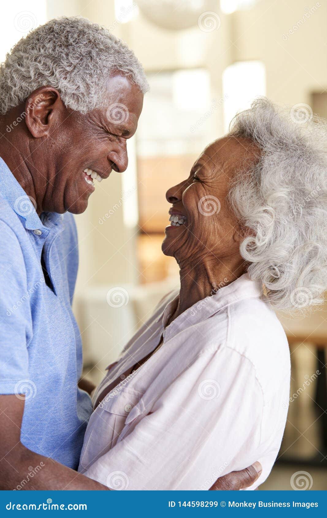 Profile Shot Loving Senior Couple Hugging At Home Together