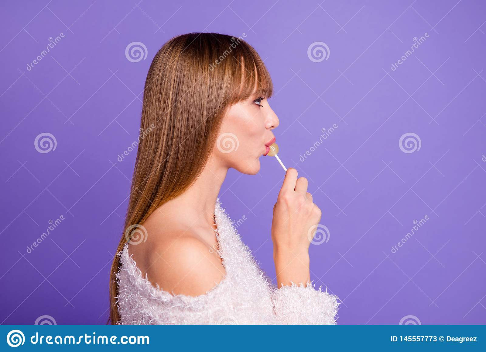 Profile side view photo nice charming lady youth hold hand yellow lolipop confectionery confident cool smart want