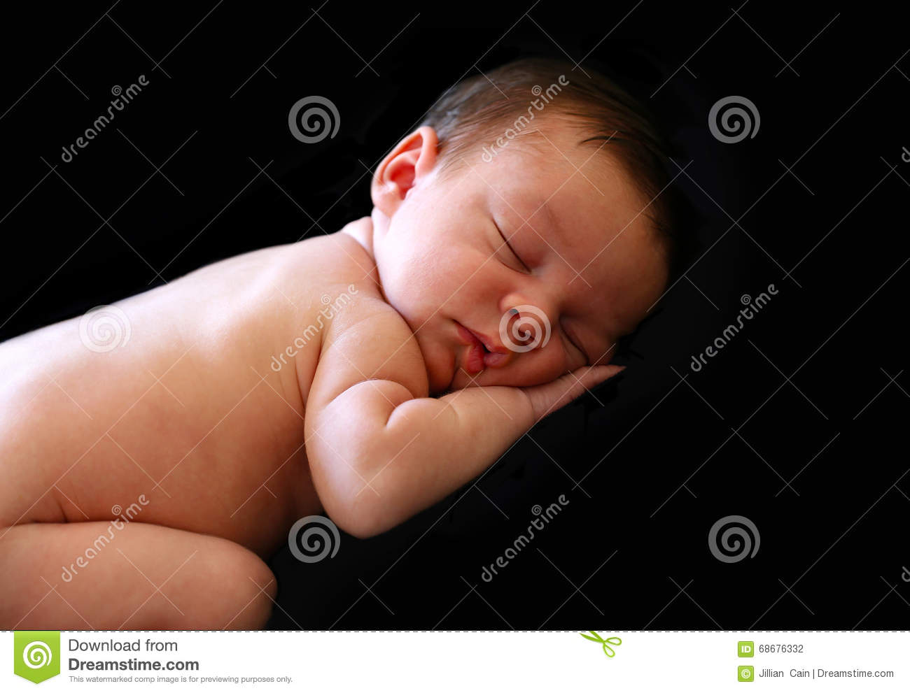 Beautiful baby sleeping at a 45 degree angle on a black background with puckered lips