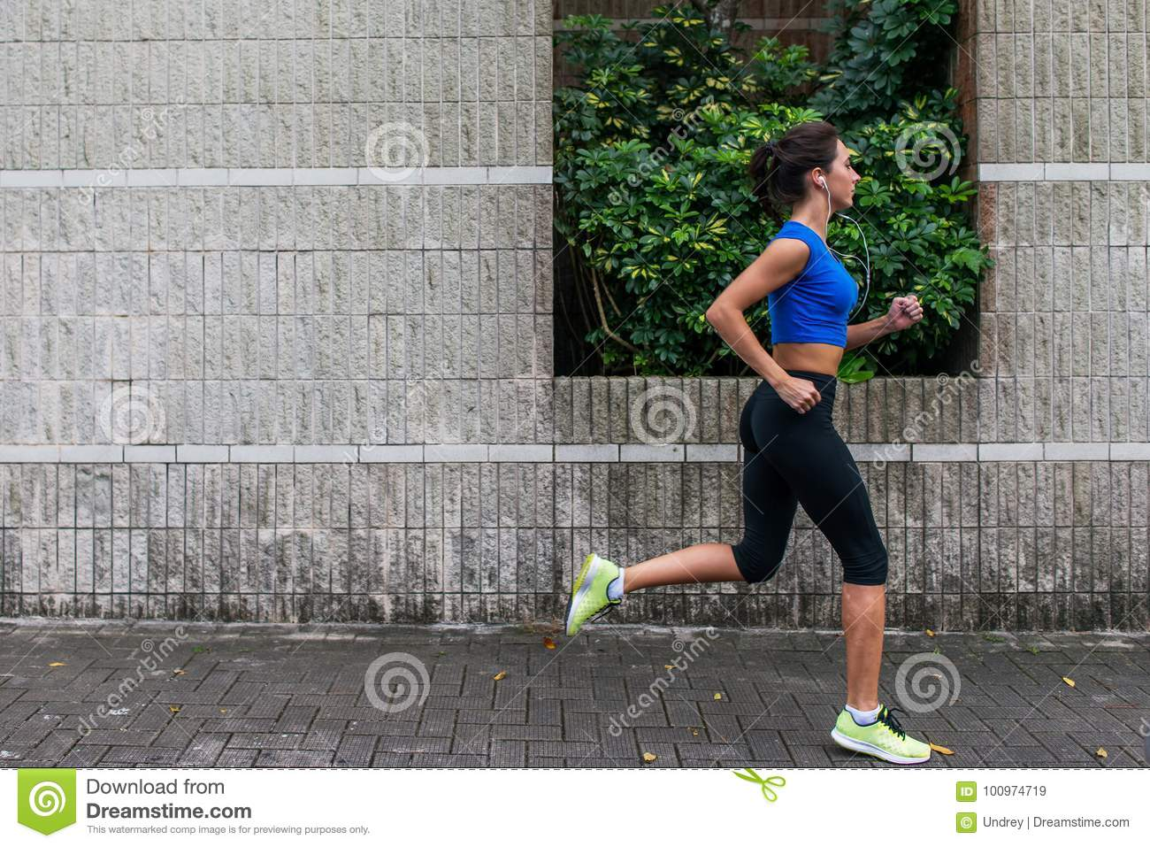 Profile view of a sporty young woman working out outdoors. Fitness girl running on sidewalk.