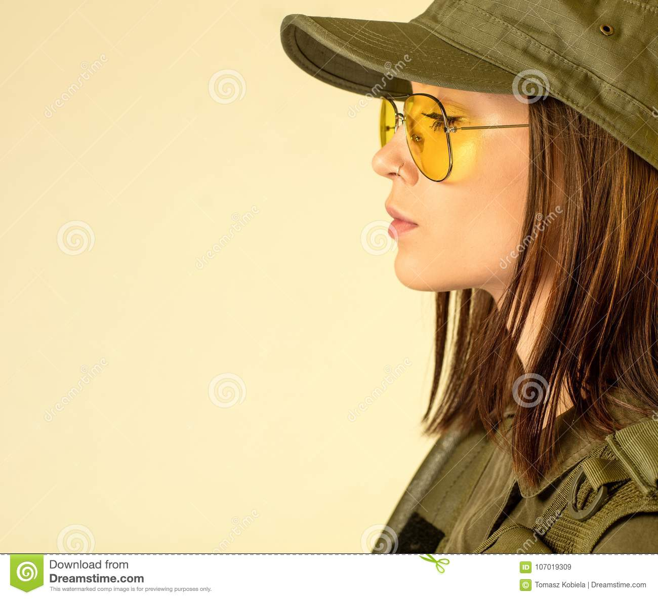 Profile of woman`s in soldier`s suit on yellow background