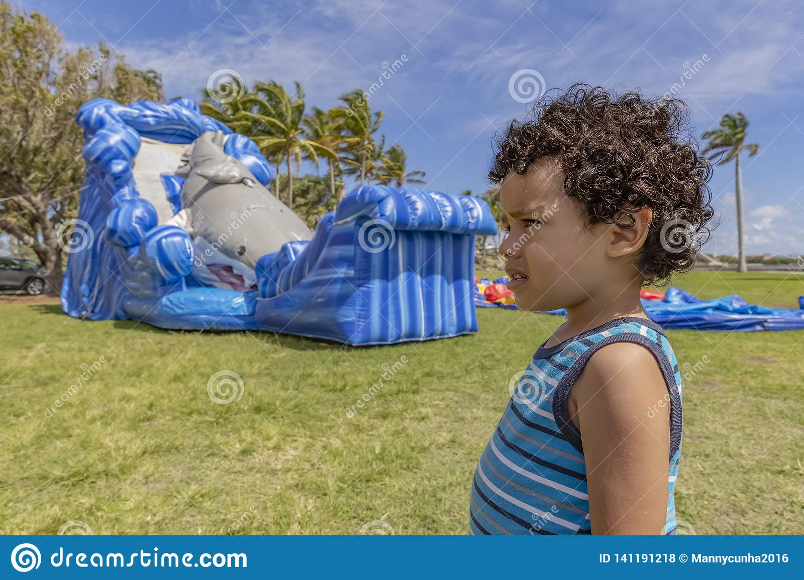 A profiled toddler stands very still with a confused look while the bounce house inflates