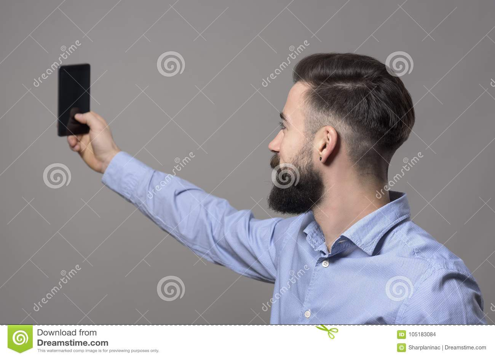 Profilera sikten av den unga moderna stiliga skäggiga affärsmannen som tar selfiefotoet med smartphonen