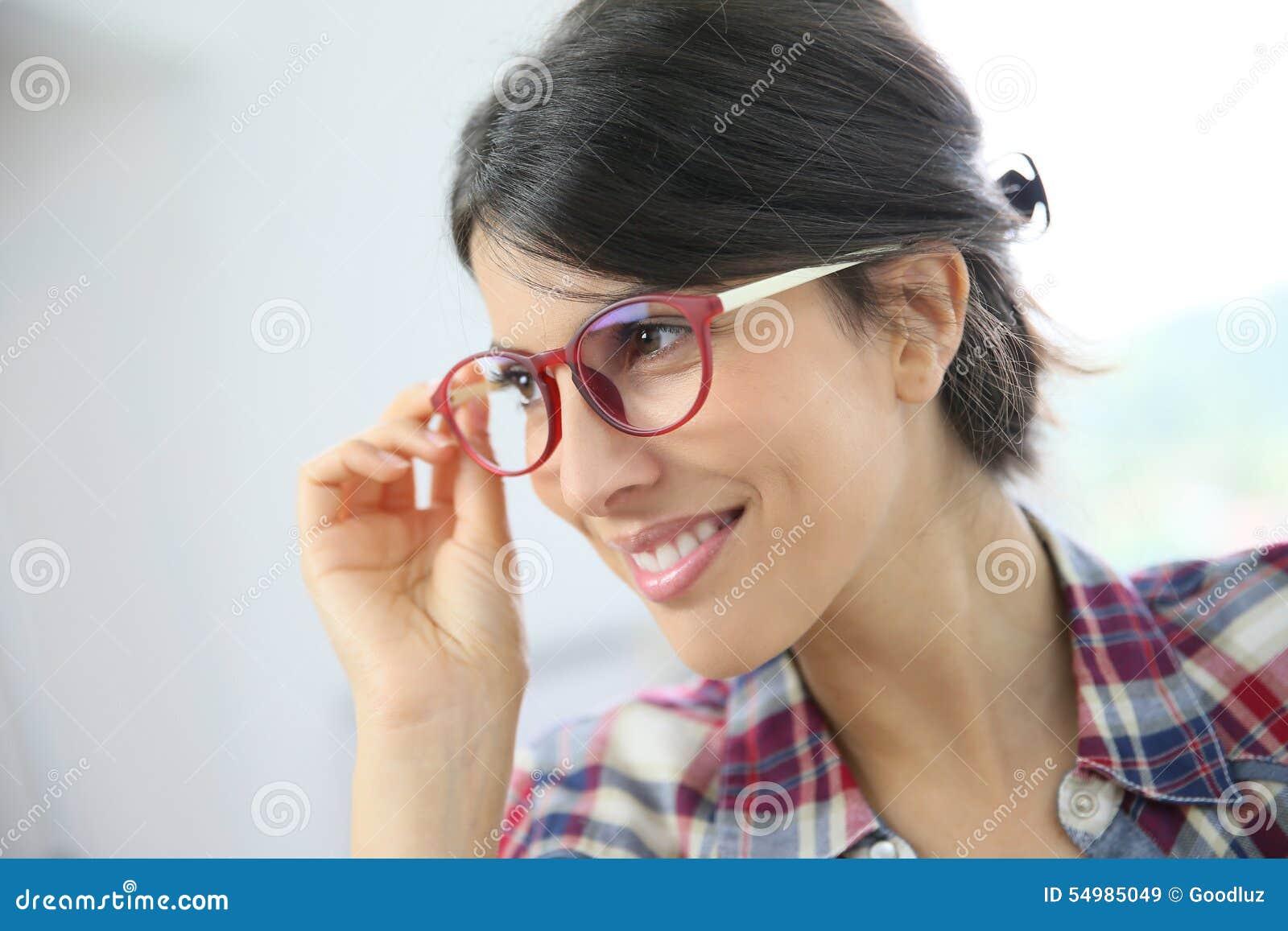 Profilera ståenden av att le bärande glasögon för den unga kvinnan