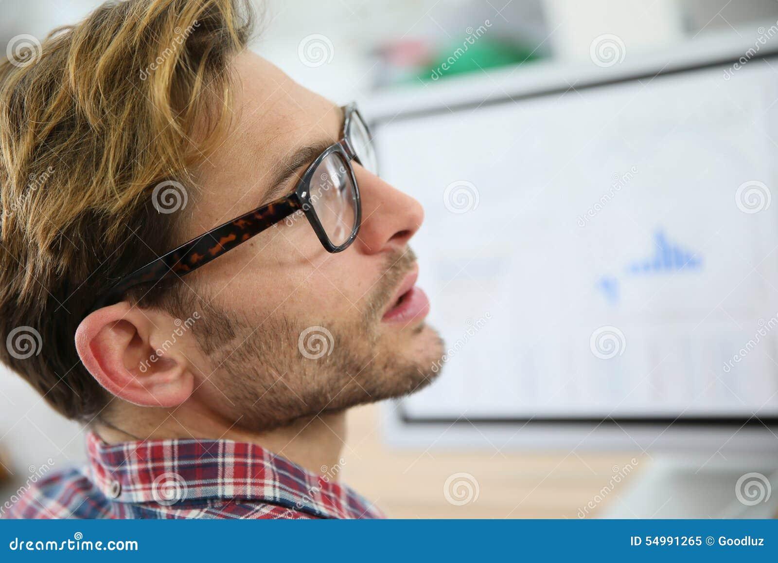 Profilera ståenden av den unga mannen på den skrivbords- datoren